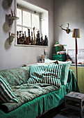 Green blankets and cushions on sofa below window with ornaments on windowsill