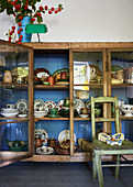 Collection of old crockery in glass-fronted cabinet