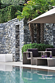 Modern seating area with stone walls next to pool