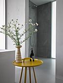 Blumen in der Vase auf gelbem Beistelltisch im modernen Bad