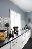 Modern country-house kitchen with patterned tiles and blue wall