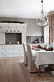 Festively set Christmas table in rustic kitchen-dining room