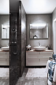 Grey modern bathroom with open-plan shower area and wide washstand