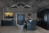 Modern log cabin with dark wooden furnishings and black fitted kitchen