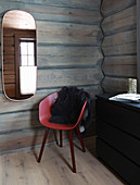 Oval mirror above red shell chair in log cabin