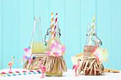 Limoflaschen mit Papierstreifen und Stoffblüten verziert