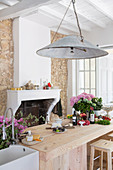 Vintage Lampe über Küchentheke aus Massivholz vor Kamin