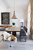 Long dining table with wooden top and various seating furniture, above it a pendant lamp