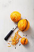 Orangen mit dem Zestenreißer und Nelken dekorieren