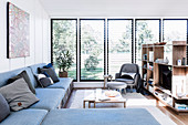 L-shaped couch with storage space and shelf as a room divider in a bright living area