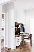 White built-in wardrobe and integrated wooden plate as a desk in the study