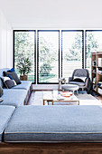 L-shaped couch, coffee table and armchair in front of window in bright living area