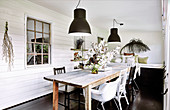 Rustic wooden table with various chairs in the dining room with white walls