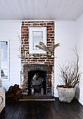 Rustikaler Backstein-Kamin im Wohnzimmer mit weiß gestrichenen Holzwänden