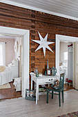 Table with drawer and chair below white star on wooden wall flanked by white door frames