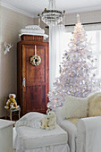White Christmas tree and white loose-covered armchair with matching footstool in front of wooden cabinet