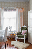 Armchair and side next to window with gauzy curtains and fairy lights