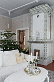 White coffee table, sofa, old tiled stove and Christmas tree in living room