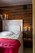 White bed and candles in rustic bedroom with wood-clad walls