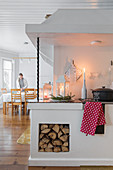 Scandinavian kitchen with wood stove and firewood niche
