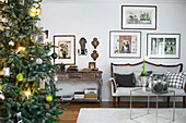 Decorated Christmas tree, couch and gallery of pictures in living room