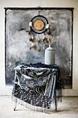 Traumfänger und bemalter Wandbehang überm Tisch