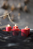 Lit red candles against grey and black background