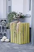 Autumnal arrangement with wooden crate made into pumpkin