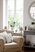 Cremefarbener Sessel am Fenster mit Deko im französischen Stil