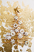 Schokoladenplätzchen mit Lavendel und Thymian am stilisierten Weihnachtsbaum hängend