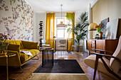 Wohnzimmer mit senfgelbem Sofa, Sideboard, Tisch mit Stühlen vor dem Fenster und Zimmerpalme