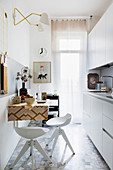 White kitchen counter, wall-mounted table and bar stools in narrow kitchen