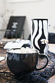 Hot drink topped with marshmallows in black cup in front of handmade tealight holder