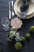 Gedeckter Tisch mit dunkler Tischwäsche, beigefarbenem Geschirr und DIY-Mooskugeln