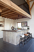 Bar stools at wood-clad kitchen counter below gallery
