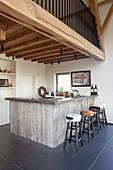 Barhocker um die Küchentheke mit Holzverkleidung unter der Galerie