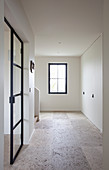 Stone-flagged floor in empty hallway with fitted white cupboards