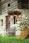 Autumnal wreath of flowers with test tubes hung from ribbons outside farmhouse