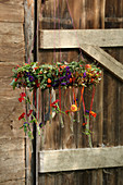 Autumnal wreath of flowers with test tubes hung from ribbons in front o ´f wooden door