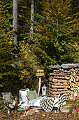 Knitted blanket and cushion on bed and standard lamp in front of stacked firewood on edge of forest
