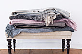 Stack of folded woollen blankets on ottoman