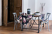 Floral fabric on rustic table and grey bistro chairs