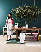 Brunette woman at the dining table with solid wood table top, houseplant above