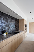 Modern fitted kitchen with wooden cabinets and black wall tiles