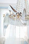 Elegant white shoes and pearl necklaces hung on chandelier