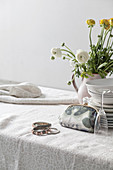 Vase of ranunculus, stacked plates, Champagne glass, make-up bag and bracelets on table