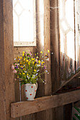 Jug of wildflowers on wooden beam