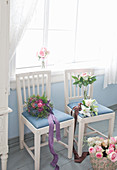 Flowers on two wooden chairs with pale blue upholstery