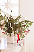 Vintage-style Christmas decorations on spruce branches in vase