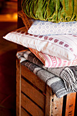 Blankets and cushions on wooden crate